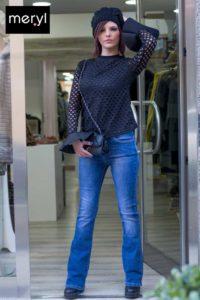 Maglia traforata con polsino in raso. Jeans a zampa e pochette in ecopelle nera con tracolla intrecciata